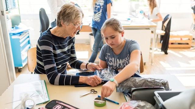 Ältere Frau hilft Mädchen bei der Handarbeit