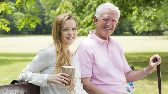 Junge Frau und älterer Herr auf Sitzbank