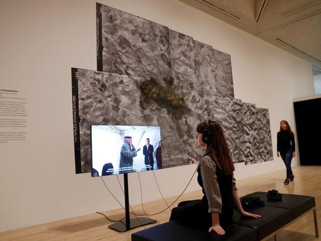Eine Frau schaut sich die Arbeit von Forensic Architecture im Tate Modern an.