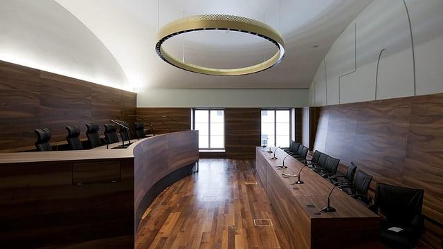 Blick in einen leeren Gerichtssaal: links die Anklagebank, rechts, leicht erhöht die Sessel der Richter.