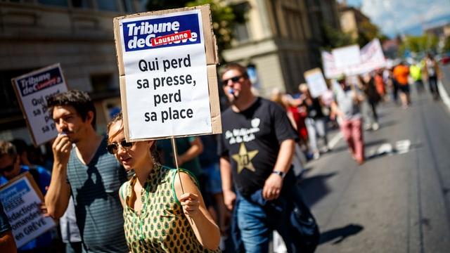Demonstrantin hält Plakat.