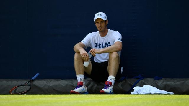 Andy Murray sitzt auf dem Court am Boden.