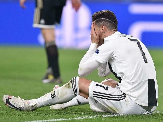 Cristiano Ronaldo sitzt enttäuscht am Boden.