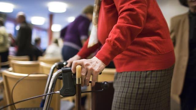 Eine ältere Dame mit Gehhilfe verlässt nach einem Klavierkonzert den Speisesaal der Altersresidenz Tertianum Huob in Pfaeffikon im Kanton Schwyz. (keystone)