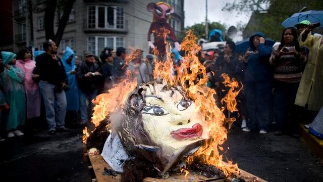 Demonstranten verbrennen während eines Protests einen Kopf Gordillos aus Pappmaché.