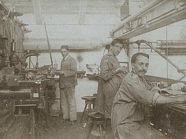 Drei Arbeiter stehen in der Versuchswerkstatt an Werkbänken.