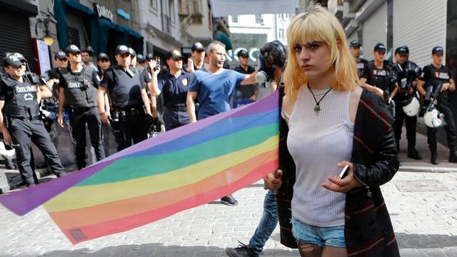 Polizisten vor einer Regenbogen-Fahne.