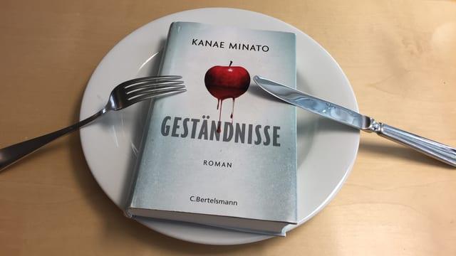 Der Thriller «Geständnisse» von Kanae Minato liegt auf einem Teller, das Besteck liegt darauf aufgestützt und impliziert ich will noch mehr