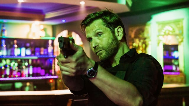Ein Mann in einer Bar, der eine Pistole hält