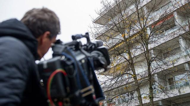 Ein Kameramann filmt einen Mietblock.