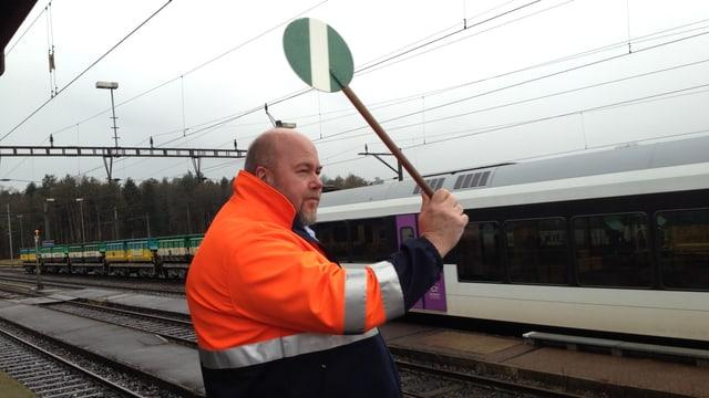 Ein Mann in oranger Leuchweste am Bahngleis schwenkt eine grün-weisse Kelle.