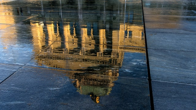 Spiegelung des Bundeshauses in einer Wasserlache.