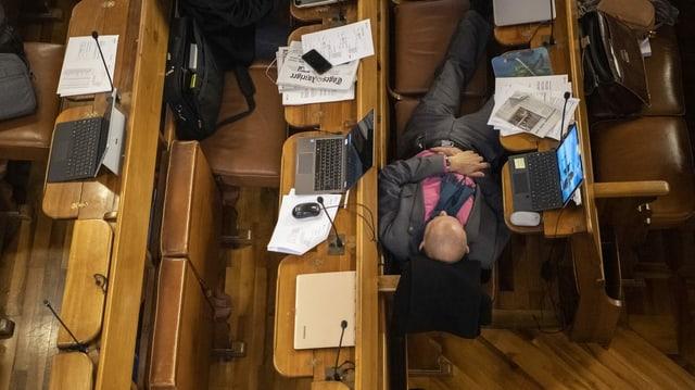 Ein Parlamentarier erholt sich auf Sitzbänken in einer Ratspause von einer Debatte