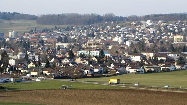 Bild auf die Gemeinde Wohlen, im Vordergrund ein Acker, im Hintergrund die Gemeinde.