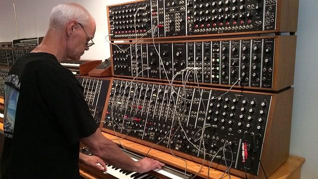 Ein Mann steht ein einem Synthesizer