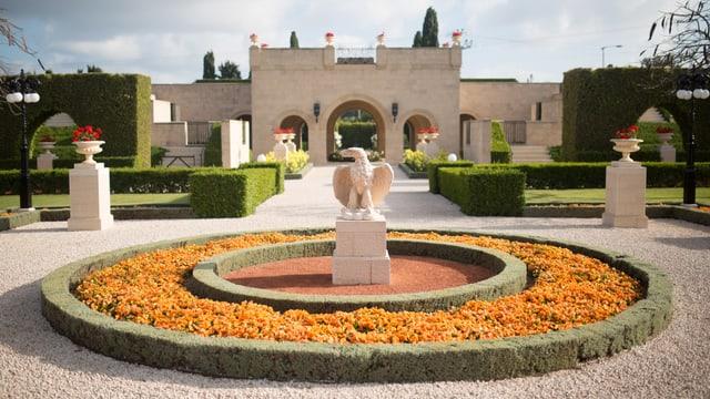 Ein weisses Gebäude, davor ist ein schöner Garten mit der Statue eines Adlers.