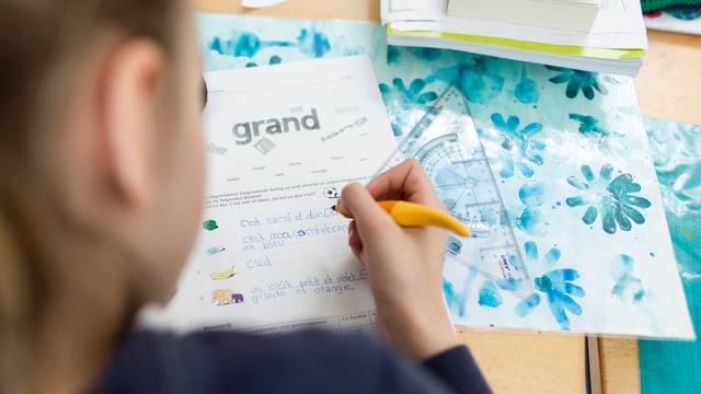 Eine Primarschülerin schreibt eine Prüfung in Französisch.