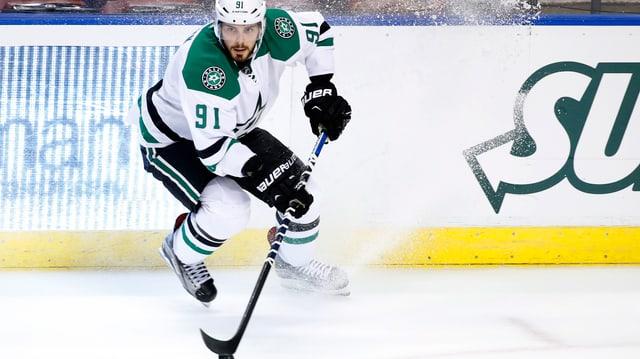 Tyler Seguin bremst in Puckbesitzt stark ab, sodass Eis hoch aufgestäubt wird.