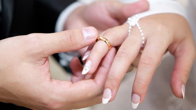 Zwei Hände, die Hand des Mannes steckt der Frau den Ring an den Finger.