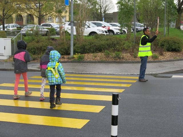 Kinder auf Fussgängerstreifen, Asylbewerber stoppt den Verkehr.