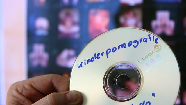 Ein Mann hält eine CD mit der Aufschrift Kinderpornografie vor einem Bildschirm.