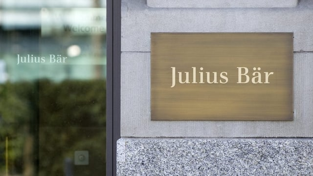 Il bajetg da la banca, sanester in vaider cun l'inscripziun Julius Bär, dretg la tabla da metal sin mir.