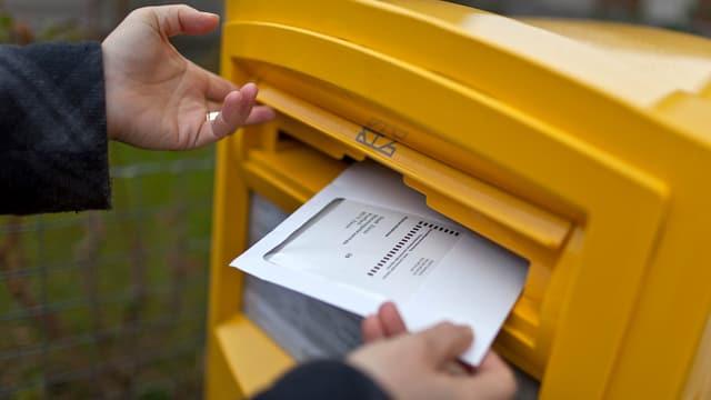 Eine Person wirft ein Wahlcouvert in einen gelben Briefkasten der Post.