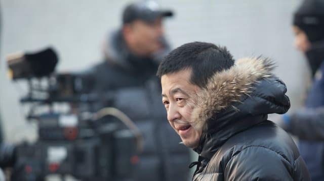 Jia Zhangke in der Daunenjacke mit Pelzkapuze bei Dreharbeiten.