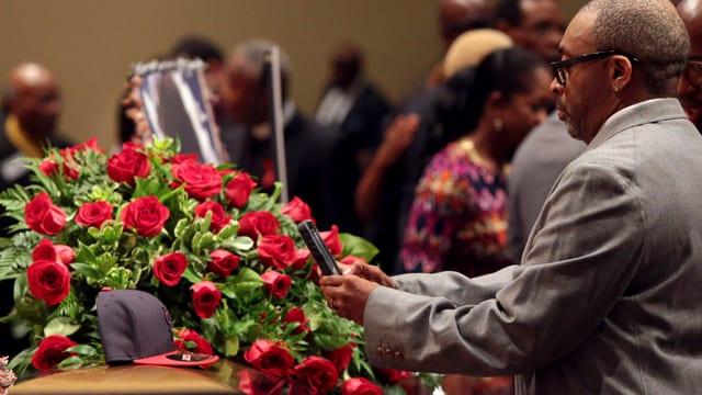 Ein Mann bei einem Rosenkranz.
