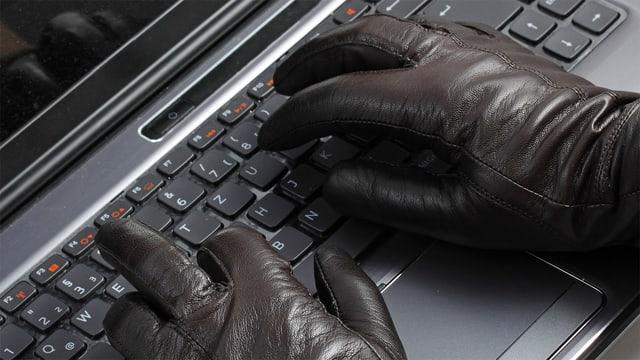Hand mit Handschuhen auf einer Computer-Tastatur.