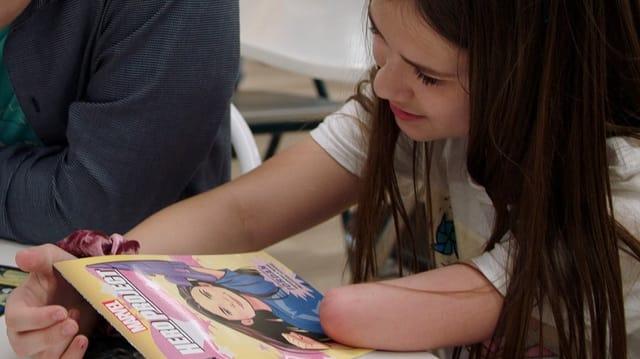 Ein Mädchen, dem ein Unterarm fehlt, schaut sich vergnügt das Comic an, in dem sie die Heldin ist.