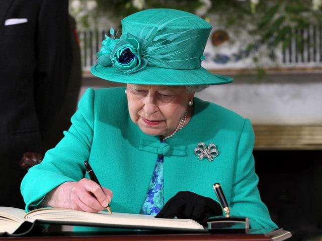 Queen Elisabeth II schreibt etwas in ein Buch