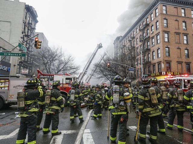 Dutzende Rettungskräfte stehen vor dem Haus. Löscharbeiten sind im Gang