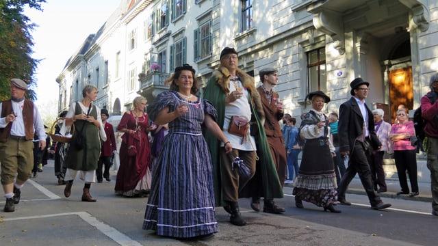 Frauen und Männer in Kostümen mit Weingläsern in den Händen.
