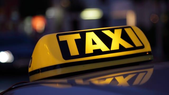 Gelbes Taxi-Schild im Dunkeln.