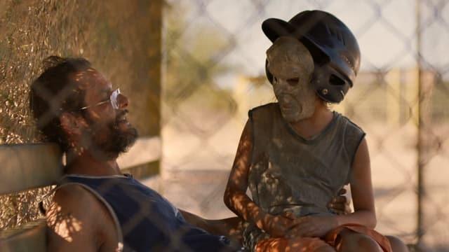 Ein Mädchen, mit einem Helm und Maske, sitzt auf dem Schoss des Vaters
