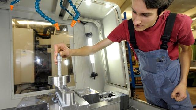 Ein junger Mann arbeitet an einre Maschine.