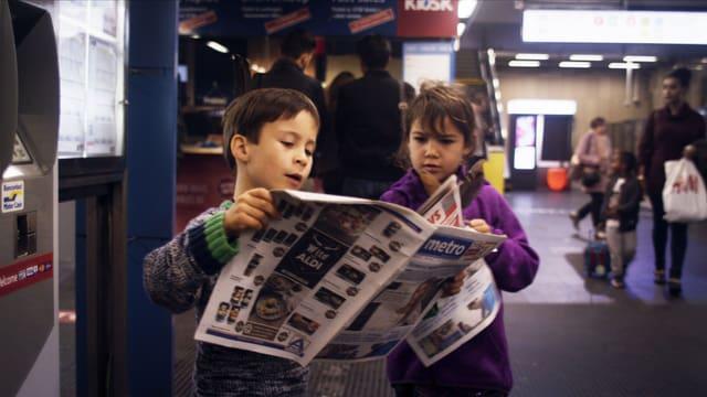 Knabe mit Zeitung in der U-Bahn.