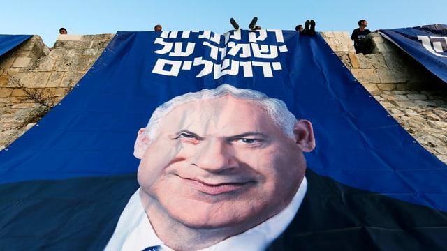 Likud-Anhänger sitzen auf der Mauer in Jerusalems Altstadt über einem riesigen Wahlplakat von Benjamin Netanjahu.