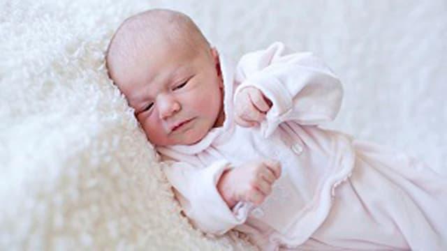 Ein Baby in rosa Babykleider
