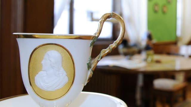 Eine Kaffeetasse mit einem Porträt und einem verzierten Halter.