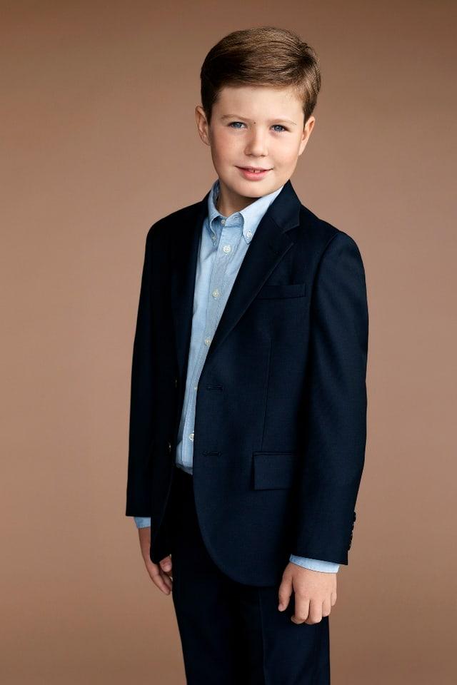 Kind mit braunen Haaren im blauen Anzug