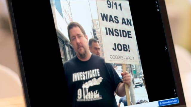 Bildschirmansicht eines Mannes, der ein Schild hält auf dem eine Verschwörungstheorie über den 11. September steht.