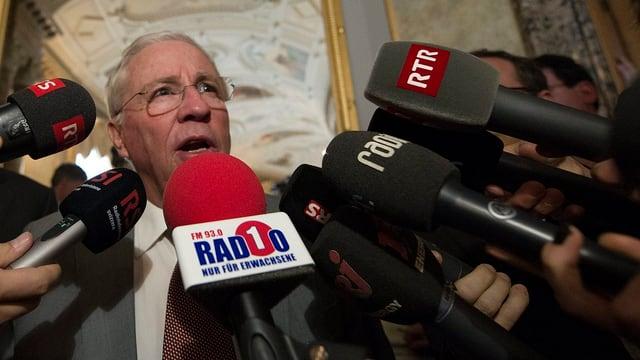 Blocher umringt von vielen Mikrofonen.