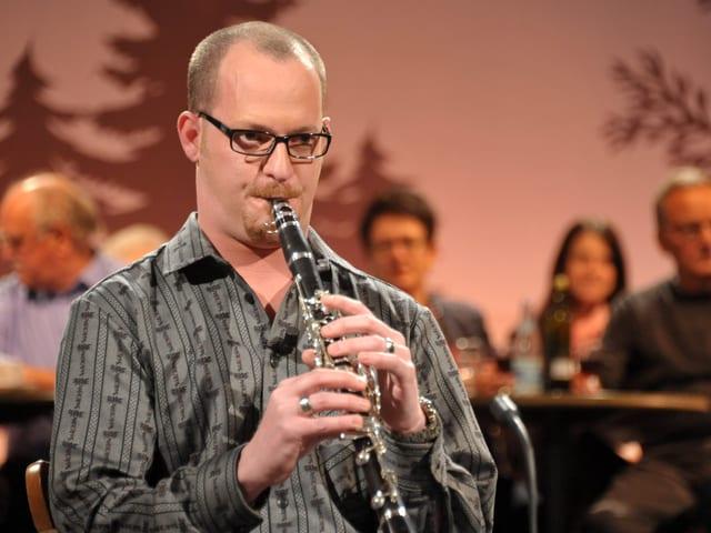 Mann speilt Blasinstrument.