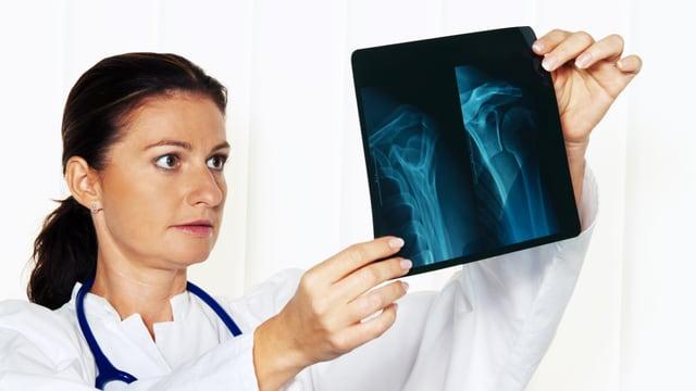 Ärztin prüft Röntgenbild