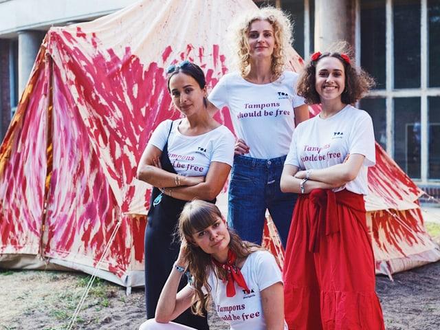 Vier junge Frauen posieren vor einem rot angemalten Zelt.