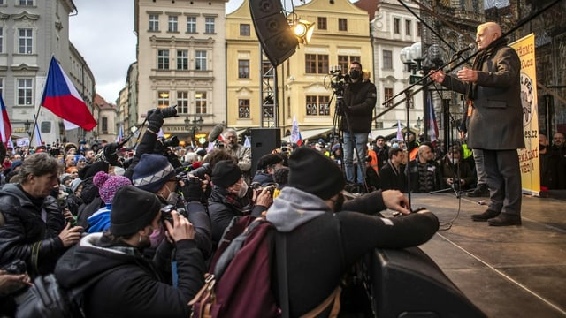 Demonstranten vor einer Bühne, auf der Vaclav Klaus eine Rede hält.