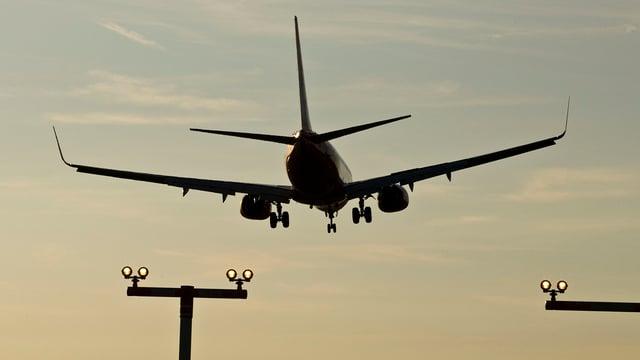 Ein Flugzeug fliegt in Abendstimmung auf den Flughafen Koten.