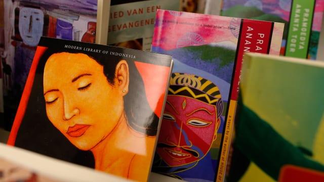 Büchertisch: Zwei bunt gestaltete Bücher mit Gesichtern auf dem Cover.